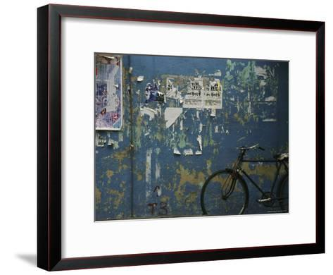 A Bicycle is Parked against a Blue Wall-Todd Gipstein-Framed Art Print