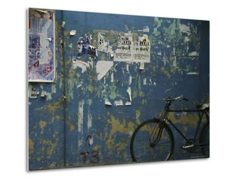 A Bicycle is Parked against a Blue Wall-Todd Gipstein-Metal Print