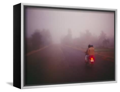 A Couple on a Motorcycle Head into Town Early in the Morning--Framed Canvas Print