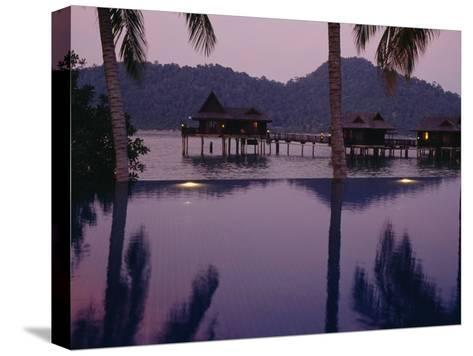 Reflections in a Pool and Traditional Malaysian Houses on Stilts--Stretched Canvas Print