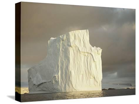 Twilight View of a Large Iceberg Under a Cloudy Sky-Bill Curtsinger-Stretched Canvas Print