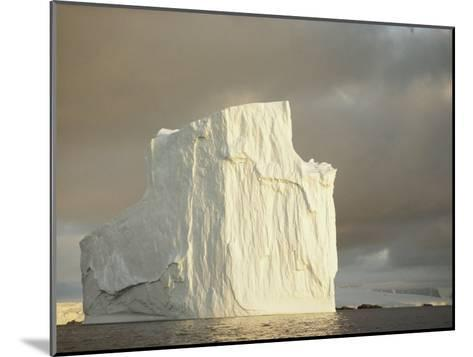 Twilight View of a Large Iceberg Under a Cloudy Sky-Bill Curtsinger-Mounted Photographic Print