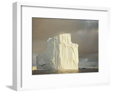 Twilight View of a Large Iceberg Under a Cloudy Sky-Bill Curtsinger-Framed Art Print