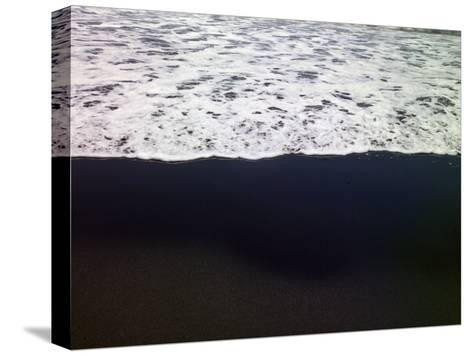 Frothy Pacific Ocean Water Pours onto a Black Sandy Beach-Raul Touzon-Stretched Canvas Print