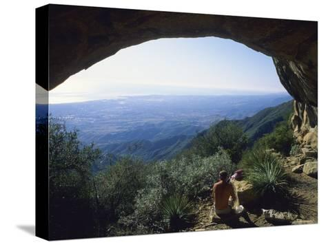 A Man at the Entrance of a Sandstone Cave on La Cumbre Peak-Rich Reid-Stretched Canvas Print