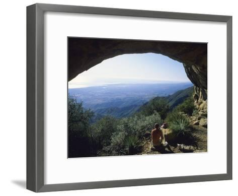 A Man at the Entrance of a Sandstone Cave on La Cumbre Peak-Rich Reid-Framed Art Print