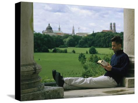 A Man Reads in the English Garden in Munich-Taylor S^ Kennedy-Stretched Canvas Print