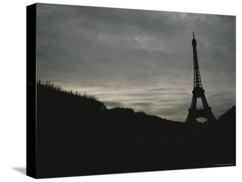 The Eiffel Tower Silhouetted against a Gray, Cloud-Filled Sky-Raul Touzon-Stretched Canvas Print