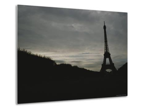 The Eiffel Tower Silhouetted against a Gray, Cloud-Filled Sky-Raul Touzon-Metal Print