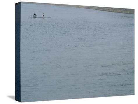 A Bicyclist is Ferried Across the Li River on a Narrow Raft-Raul Touzon-Stretched Canvas Print