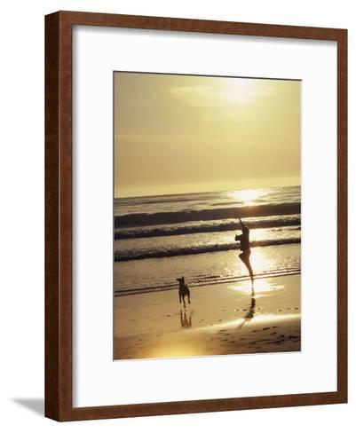 A Pet Dog Runs with its Owner on a Beach-Bill Curtsinger-Framed Art Print