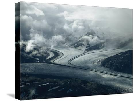 Branches of a Glacier Join Together Below Cloud-Covered Peaks-George F^ Mobley-Stretched Canvas Print