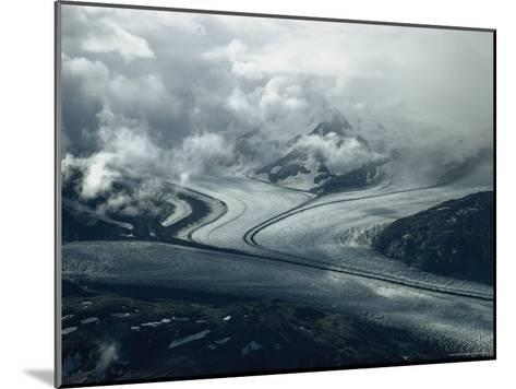 Branches of a Glacier Join Together Below Cloud-Covered Peaks-George F^ Mobley-Mounted Photographic Print