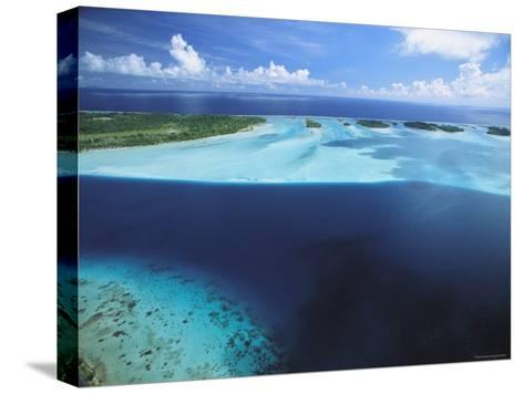 Clear Blue Water Surrounds Small Pacific Islands-Tim Laman-Stretched Canvas Print