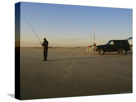 A Man Holds a Fishing Pole While Standing Near His Jeep Truck-Stephen Alvarez-Stretched Canvas Print