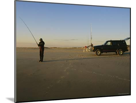 A Man Holds a Fishing Pole While Standing Near His Jeep Truck-Stephen Alvarez-Mounted Photographic Print