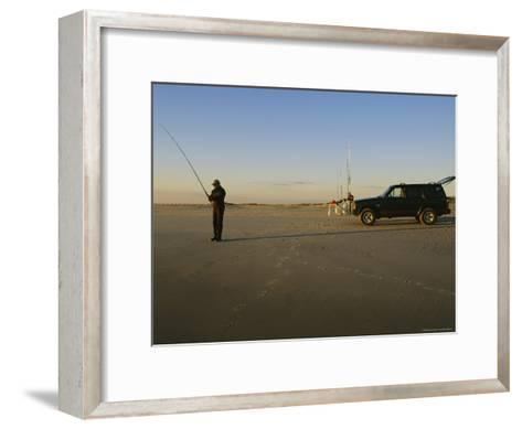 A Man Holds a Fishing Pole While Standing Near His Jeep Truck-Stephen Alvarez-Framed Art Print