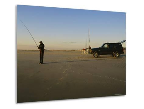 A Man Holds a Fishing Pole While Standing Near His Jeep Truck-Stephen Alvarez-Metal Print