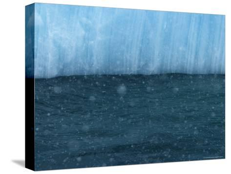 Snow Flakes Drifting Past a Blue Iceberg-Ralph Lee Hopkins-Stretched Canvas Print