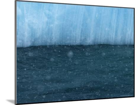 Snow Flakes Drifting Past a Blue Iceberg-Ralph Lee Hopkins-Mounted Photographic Print