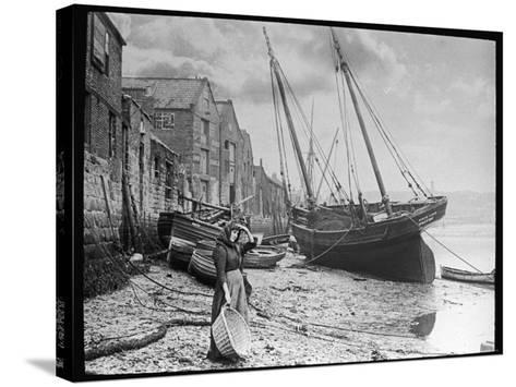 Young Woman in Headscarf and Working Clothes Looks out to Sea from the Shoreline--Stretched Canvas Print