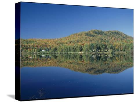 A Lake Surrounded by Trees Displaying the Colors of Autumn-Richard Nowitz-Stretched Canvas Print