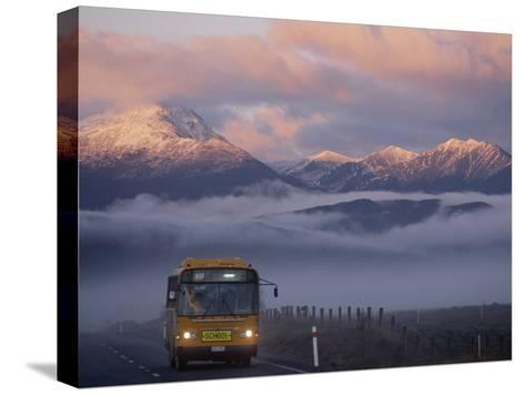 Bus at Sunrise with the Mountains Covered in a Blanket of Fog-Annie Griffiths-Stretched Canvas Print