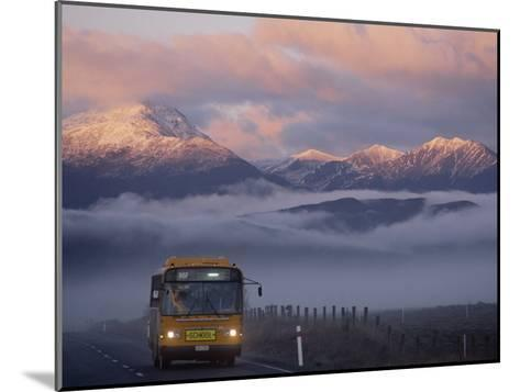 Bus at Sunrise with the Mountains Covered in a Blanket of Fog-Annie Griffiths-Mounted Photographic Print