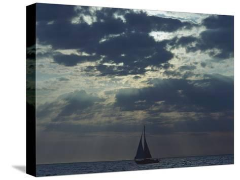 Sunlight Breaks Through a Cloudy Sky onto a Sailboat at Sea-Todd Gipstein-Stretched Canvas Print