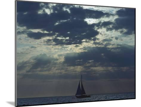 Sunlight Breaks Through a Cloudy Sky onto a Sailboat at Sea-Todd Gipstein-Mounted Photographic Print