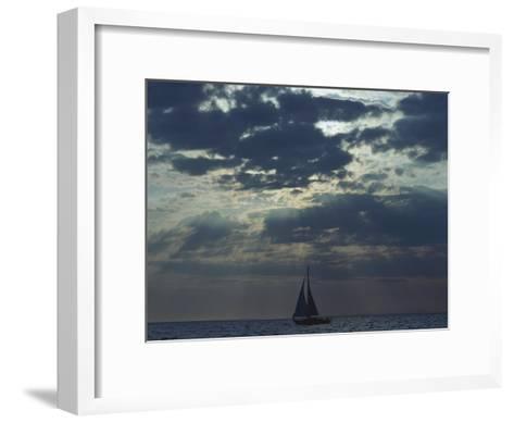 Sunlight Breaks Through a Cloudy Sky onto a Sailboat at Sea-Todd Gipstein-Framed Art Print