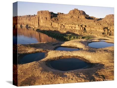 View of Water-Filled Depressions in Rock Formations Near the Colorado River-Stephen Alvarez-Stretched Canvas Print