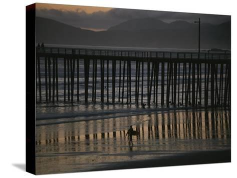 A Surfer Walks up the Beach Near a Pier at Twilight-Michael S^ Lewis-Stretched Canvas Print