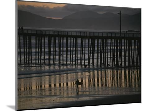 A Surfer Walks up the Beach Near a Pier at Twilight-Michael S^ Lewis-Mounted Photographic Print