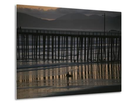 A Surfer Walks up the Beach Near a Pier at Twilight-Michael S^ Lewis-Metal Print