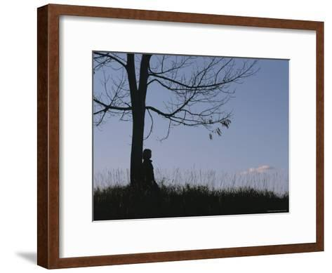 A Young Girl Leans against a Leaf-Less Tree on a Hill-Roy Gumpel-Framed Art Print