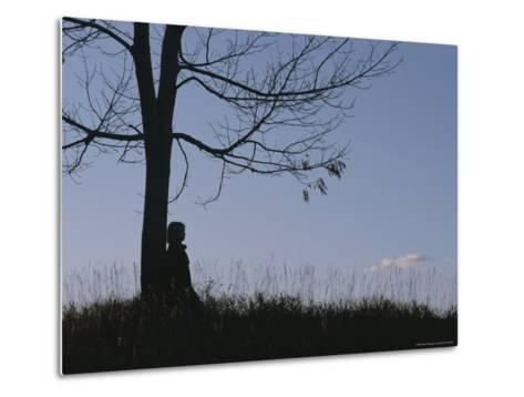 A Young Girl Leans against a Leaf-Less Tree on a Hill-Roy Gumpel-Metal Print