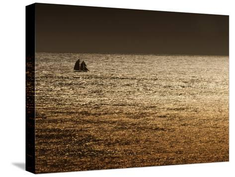A Sailing Ship Crosses Waters Turned Gold by the Setting Sun-Sam Abell-Stretched Canvas Print