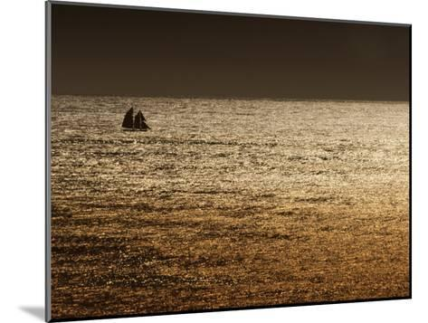 A Sailing Ship Crosses Waters Turned Gold by the Setting Sun-Sam Abell-Mounted Photographic Print