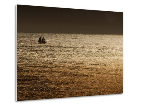 A Sailing Ship Crosses Waters Turned Gold by the Setting Sun-Sam Abell-Metal Print