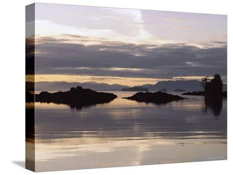 Islands and Clouds Reflect on a Calm Sea at Kah Shakes Cove-Bill Curtsinger-Stretched Canvas Print