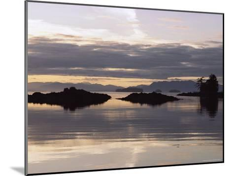 Islands and Clouds Reflect on a Calm Sea at Kah Shakes Cove-Bill Curtsinger-Mounted Photographic Print