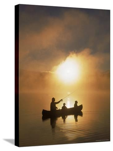 People Fishing from Canoe at Sunset-Bob Winsett-Stretched Canvas Print