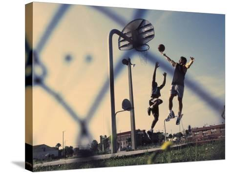 Low Angle View of Two Men Playing Basketball--Stretched Canvas Print