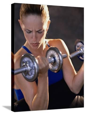 Young Woman Exercising with Dumbbells--Stretched Canvas Print