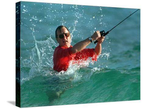 Waves Splash President-Elect George Bush as He Casts a Line While Surf-Fishing--Stretched Canvas Print