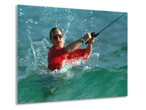 Waves Splash President-Elect George Bush as He Casts a Line While Surf-Fishing--Metal Print