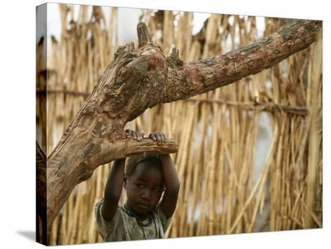 A Sudanese Girl Plays Inside a Thatched Hut at the Refugee Camp of Zamzam--Stretched Canvas Print