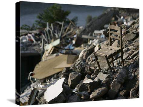 A Chair is Seen on the Rubble of a Collapsed Apartment Complex--Stretched Canvas Print