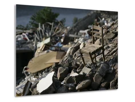 A Chair is Seen on the Rubble of a Collapsed Apartment Complex--Metal Print
